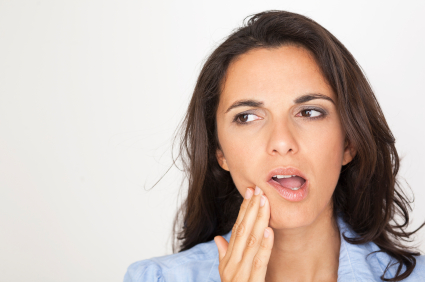 Woman holding jaw due to gum pain